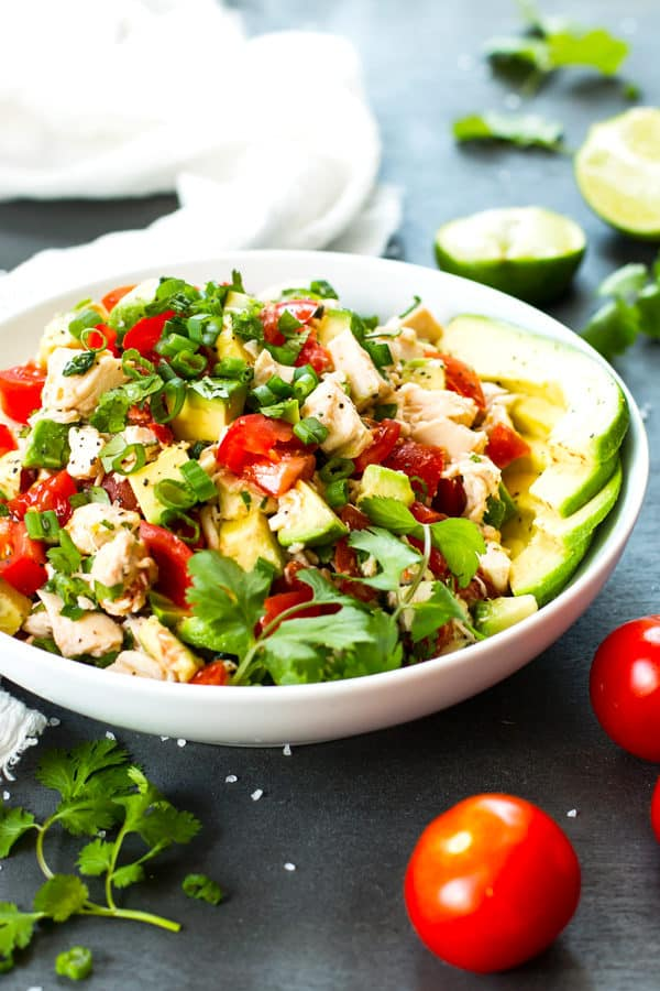 A Tomato and Avocado Chicken Salad in a white bowl with limes and cilantro on the side.