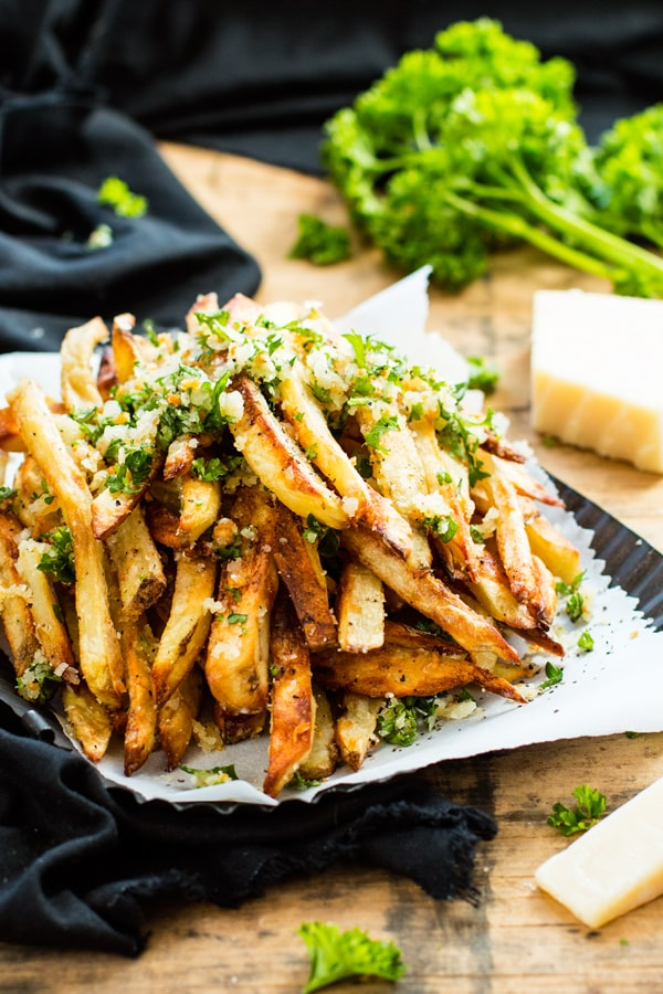 Gluten-free garlic fries in a pile on white parchment paper for a delicious side dish.