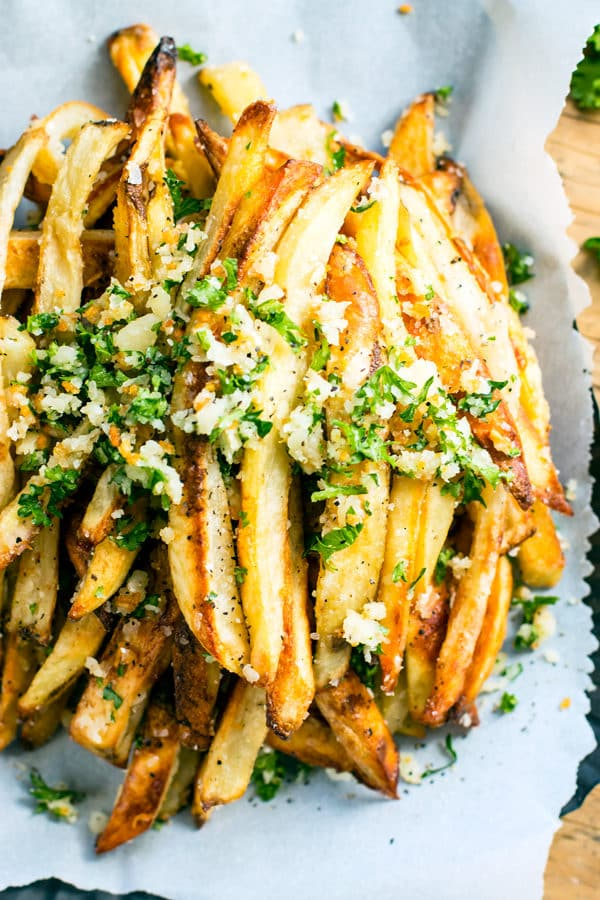 A pile of crispy fries on parchment paper ready for a delicious lunch.