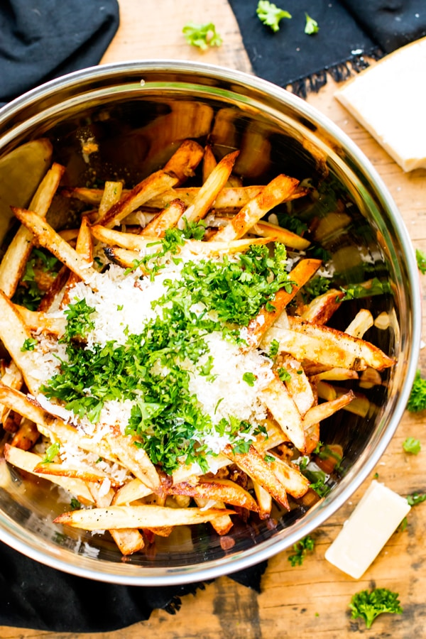Homemade Fries in a silver container topped with Parmesan, garlic, and parsley.