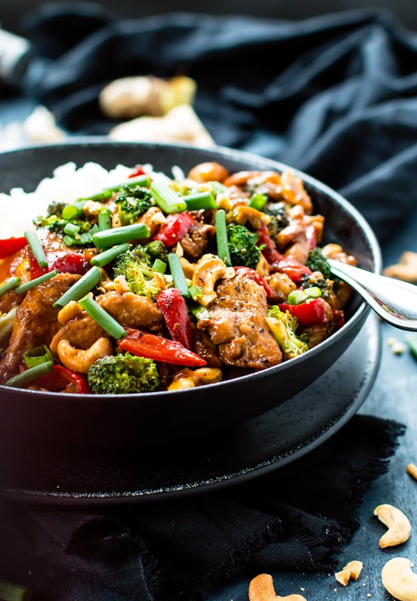 Cashew Chicken Stir-Fry in a bowl with rice and a fork for a healthy lunch.