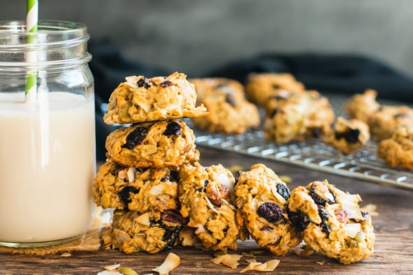 Gluten-free trail mix cookies in a stack next to a glass of milk.