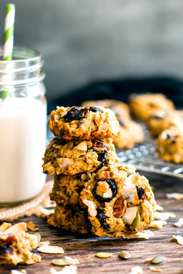 A collection of Oatmeal Trail Mix Cookies with a glass of milk next to a cooling rack.