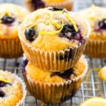 Healthy lemon muffins with blueberries stacked on top of each other on a cooling rack.