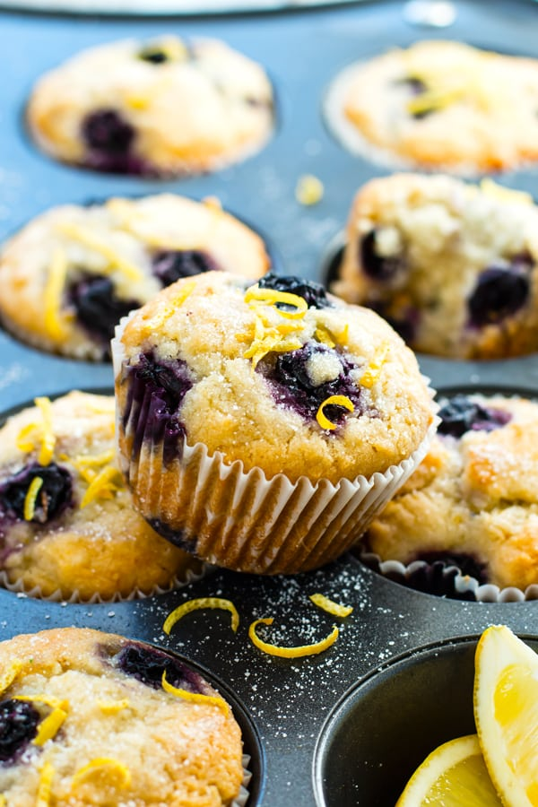 A healthy blueberry muffin recipe sitting on top of a muffin pan with lemons.