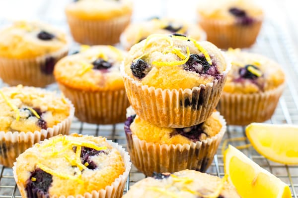 Gluten-free lemon blueberry muffins on a cooling rack topped surrounded by lemon slices.