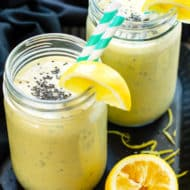 Two glasses filled with a turmeric smoothie recipe using lemon, bananas, and other fresh ingredients.
