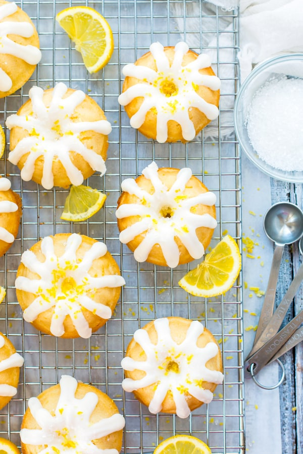 An overhead picture of a lemon bundt cake recipe with mini cakes on a cooling rack.
