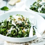 Mixed greens with spinach and kale in a white bowl for a light lunch.