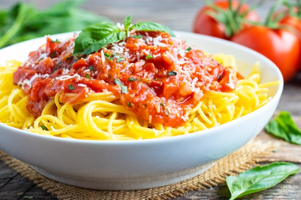 A white bowl full of spaghettie pomodoro with Parmesan cheese and basil on top.