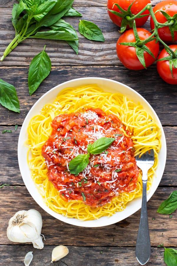 Pomodoro sauce recipe on a bed of gluten-free spaghetti in a white bowl.