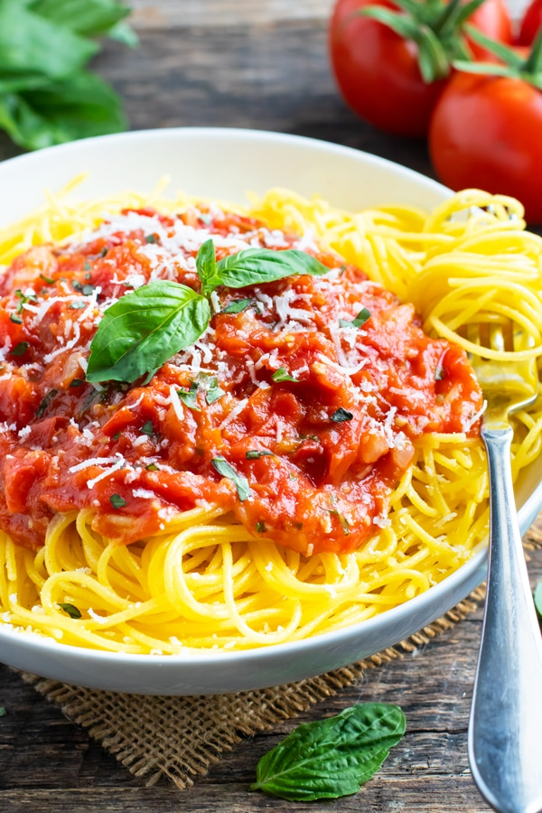 A white bowl full of spaghetti with pasta pomodoro sauce and basil.