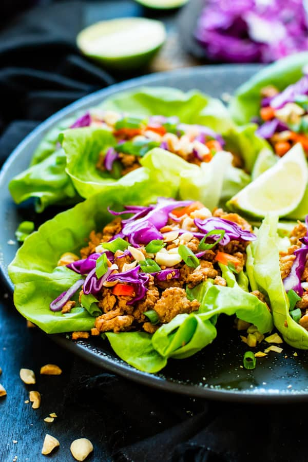 A plate full of gluten-free Ground Chicken Thai Lettuce Wraps with lime wedges for lunch.