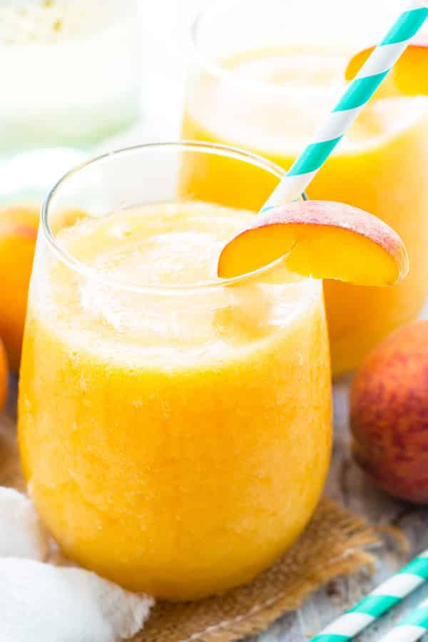 Two glasses filled with Frozen Peach White Wine Sangria for a delicious summer treat.