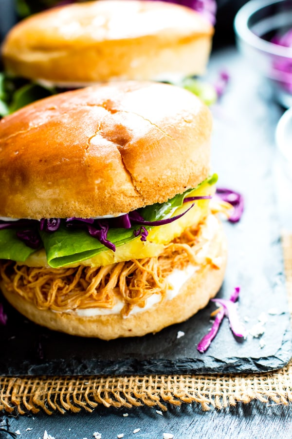Whip up a batch of these slow cooker Hawaiian chicken sandwiches for your next potluck or get-together! These shredded pineapple chicken sandwiches are a super easy, healthy, and gluten-free lunch or dinner recipe the whole family will love!