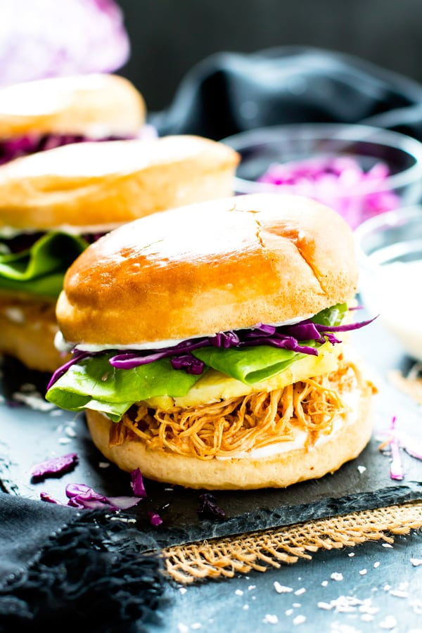 A pulled chicken sandwich with pineapple and lettuce in a bun.