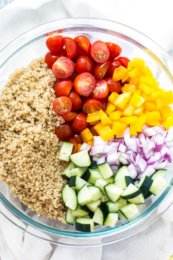 A glass bowl filled with fresh vegetables to create a Summer Vegetable Quinoa Salad.