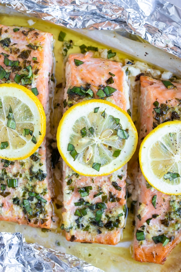 A close-up image of a lemon basil baked salmon recipe that has been baked in foil packets.