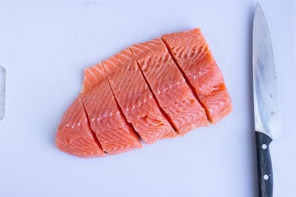 A pound of salmon cut into fillets.