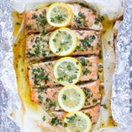Baked basil salmon wrapped in foil and topped with lemon slices.