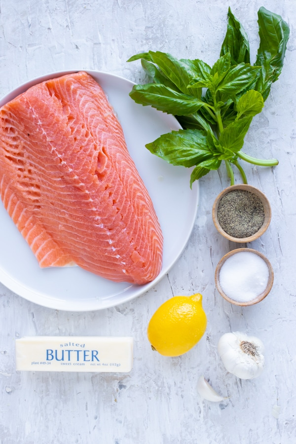 A pound of salmon, fresh basil, a lemon, garlic, salt, pepper, and butter - showing ingredients.