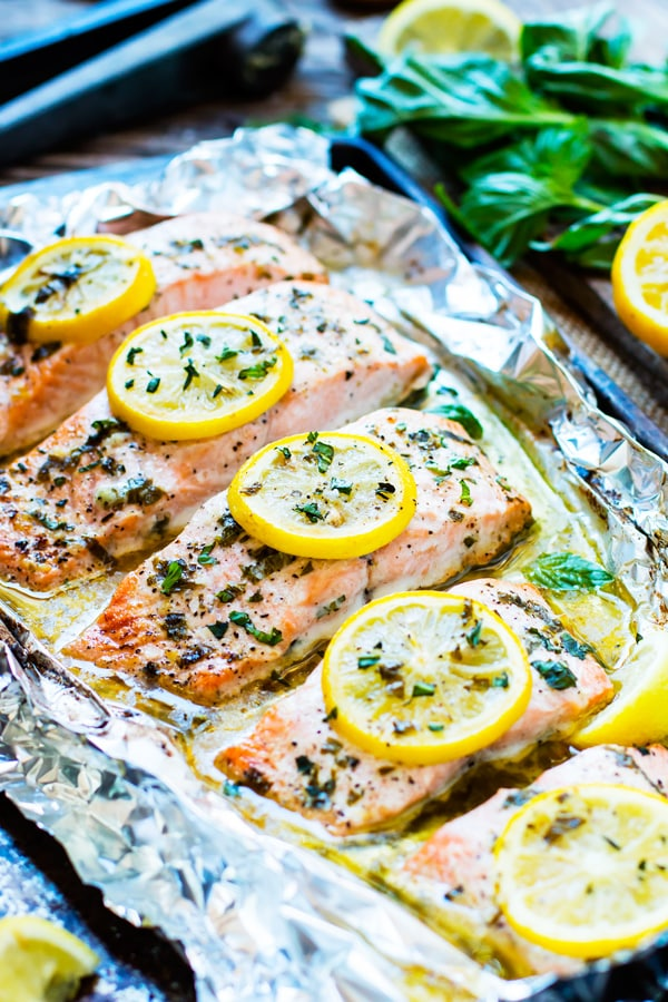 Easy baked salmon recipe with lemons on a baking sheet lined with foil.
