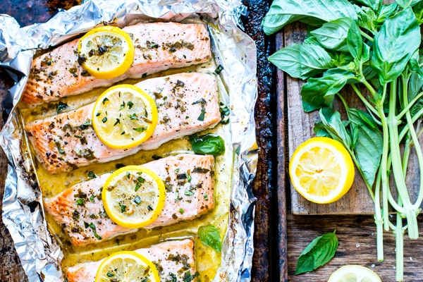 A row of Basil & Lemon Baked Salmon on a baking sheet lined with foil.
