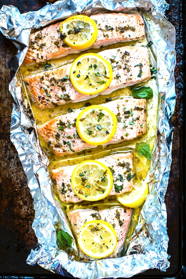 An overhead picture of a healthy salmon recipe with lemon slices and fresh herbs.