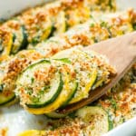 A serving spoon scooping out baked squash and zucchini casserole from a white casserole dish.