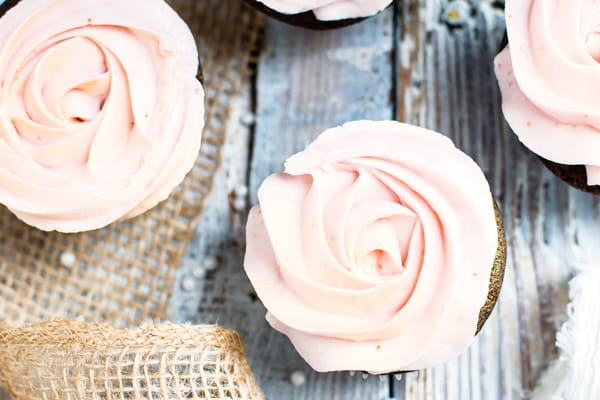 Gluten-free chocolate cake cupcakes with strawberry frosting on a table.