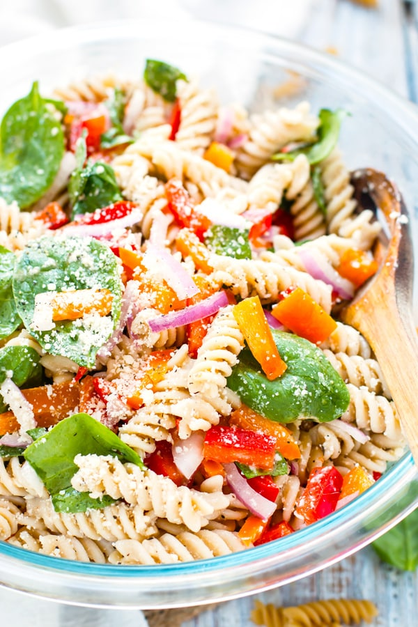 Easy pasta salad in a bowl with fresh basil and tomatoes for a summer lunch.