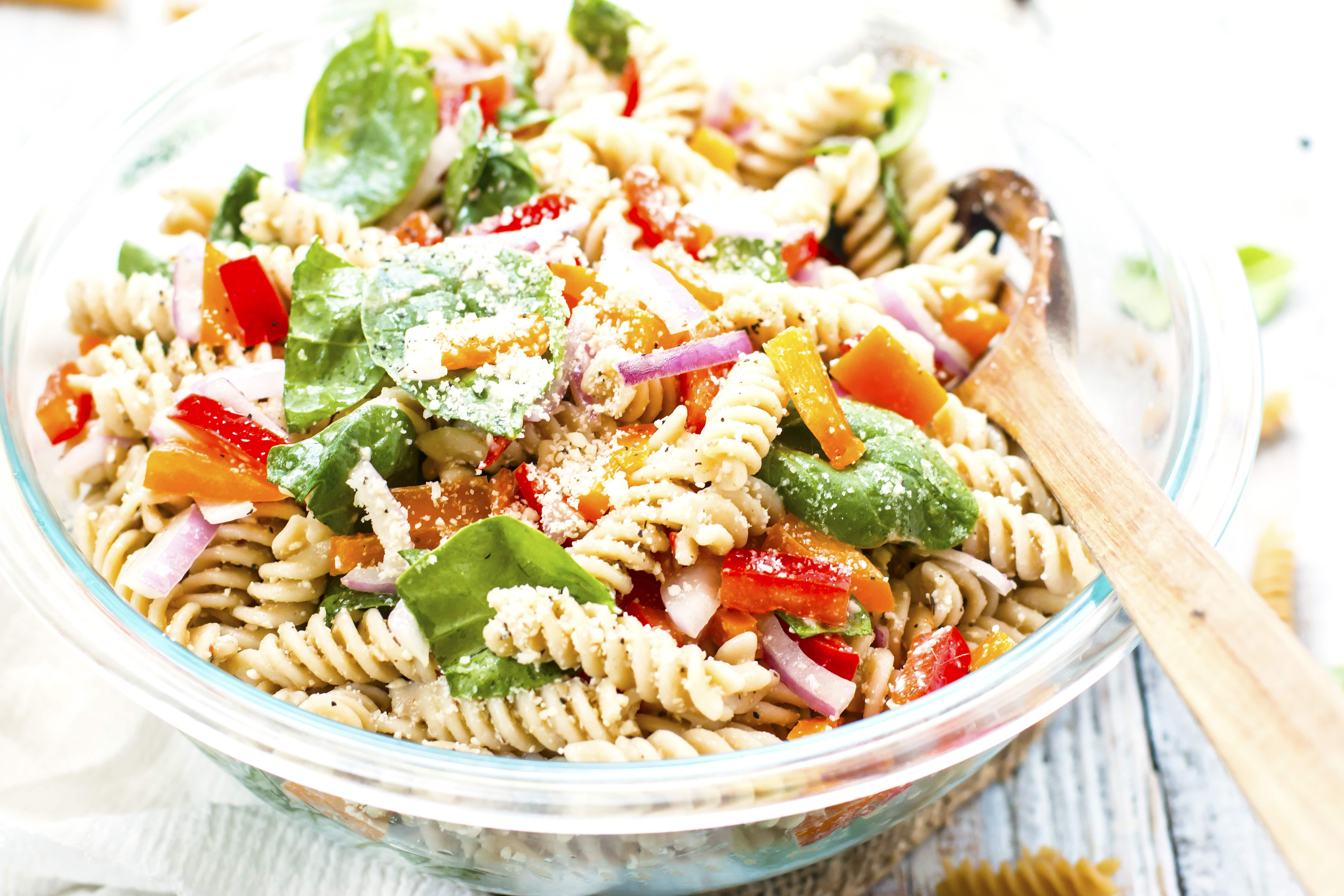 Gluten-free pasta salad with Italian dressing in a glass bowl for a summer party.
