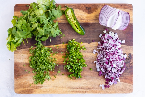 Finely chopped cilantro, jalapeno, and red onion on a wooden cutting board.