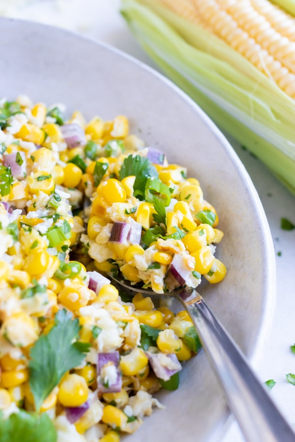 A silver spoon scooping out a bite of a street corn salad with cilantro and red onions and a corn cob in the background.