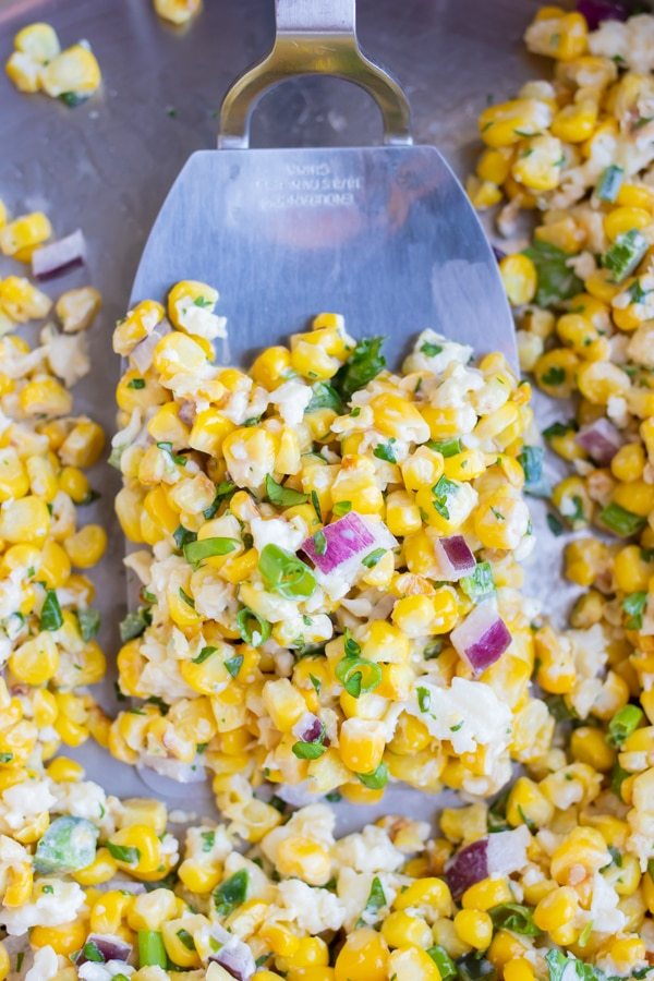 A stainless steel spatula scooping up a serving of a corn salad recipe as a side dish.