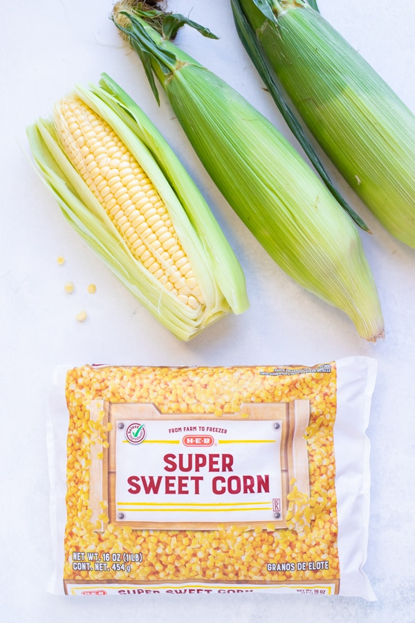 Fresh corn on the cob with husks and a frozen sweet corn bag.