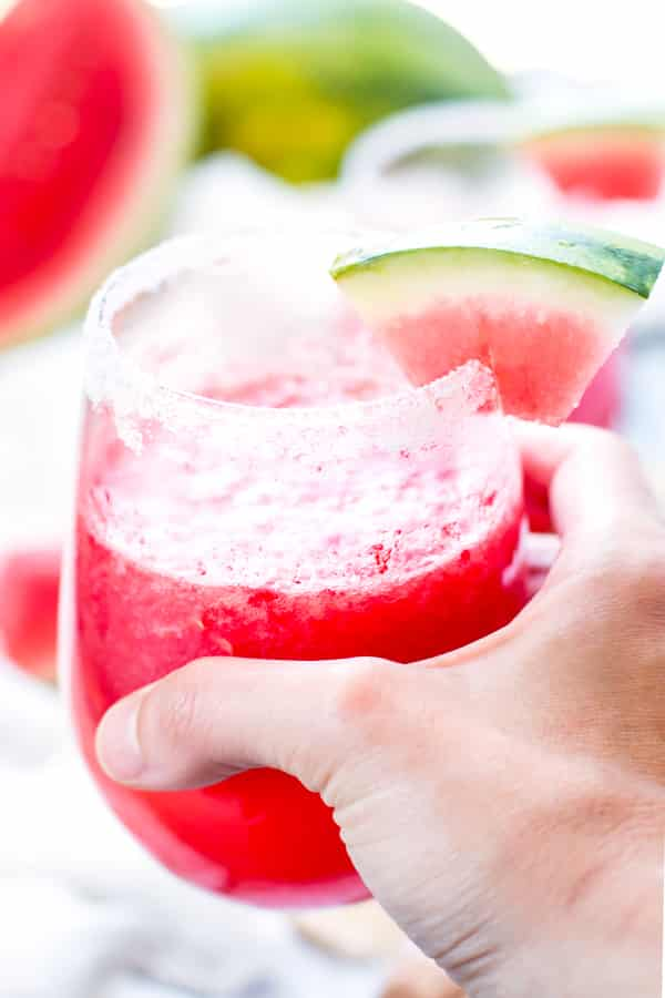 A hand holding a watermelon drink made with tequila and Champagne with a slice of watermelon on the side.