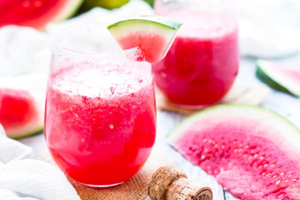 Two glasses of a tequila cocktail recipe with a slice of watermelon for an easy drink.