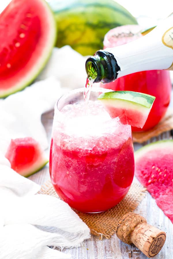 Pouring Champagne into a single tequila drink with watermelon for an adult beverage.