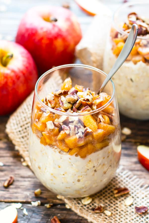 Apple overnight oats made with cinnamon in a glass with a spoon.