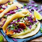 Gluten-free cod fish tacos with lime slices on a table.