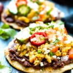 Pile up your favorite Mexican food inspired fixings on these super quick breakfast tostadas!!  Toasted corn tortillas are loaded with eggs, black beans, avocado, and pico de gallo for an awesome way to start your morning.