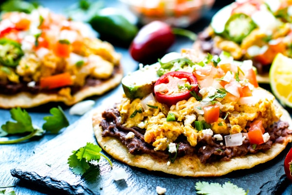 Gluten-free Mexican tostadas on a blue slab topped with fresh vegetables.