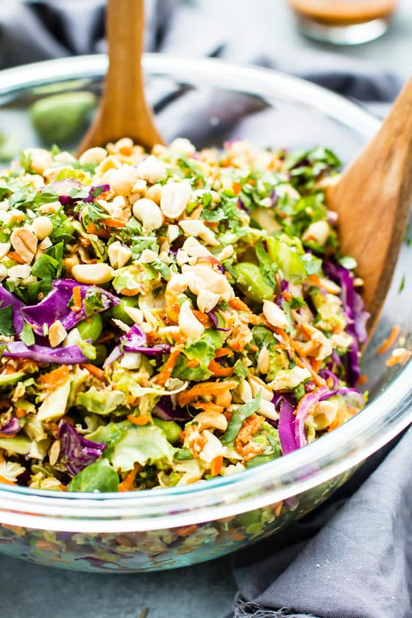 Thai Salad recipe in a glass bowl with two wooden spoons for a healthy lunch.