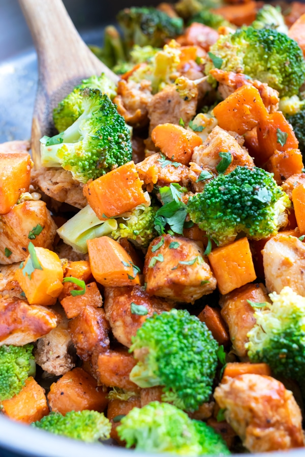Cubed sweet potatoes, broccoli florets, and chicken breasts in a pot with a wooden spatula.