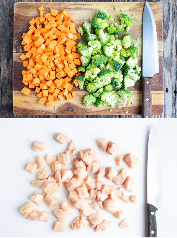 Cubed sweet potatoes, broccoli florets, and chicken breasts on cutting boards.