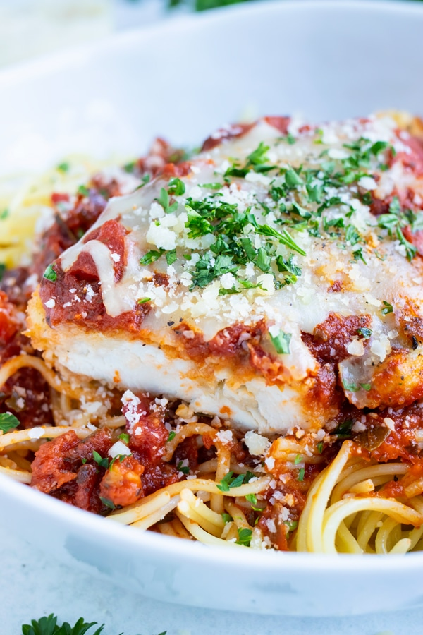 Chicken is juicy and covered with a delicious crusted outside and topped with cheese and tomato sauce.