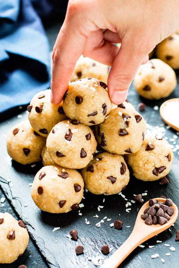 A pair of fingers picking up a ball of chocolate chip energy bites with a wooden spoon.