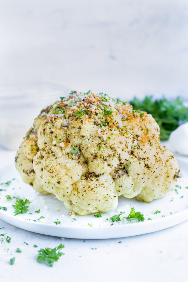 Serve garlic and herb whole roasted cauliflower at your next Thanksgiving or Christmas dinner party!