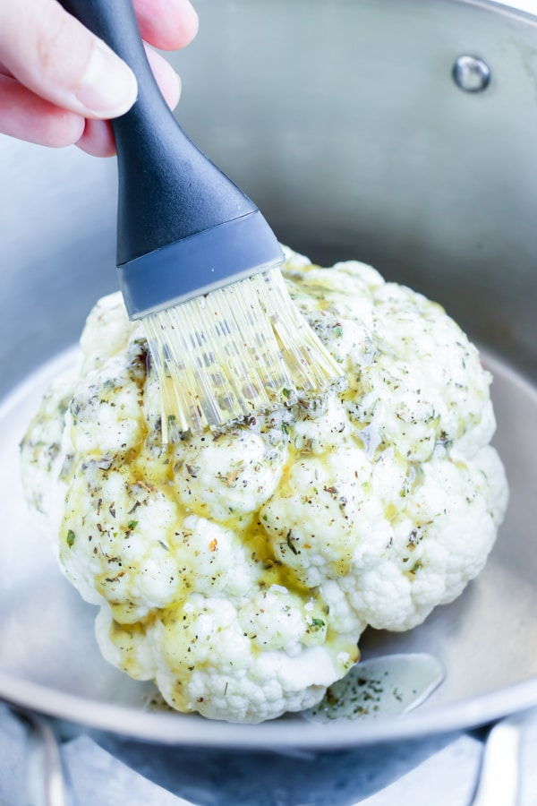 Whole baked cauliflower is brushed with a garlic herb butter.